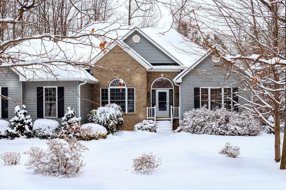 Maison couleurs claires sous la neige avec arbres au premier plan